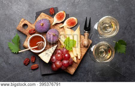 Antipasto plate with cheese, figs and grapes. Appetizer board and white wine. Top view flat lay