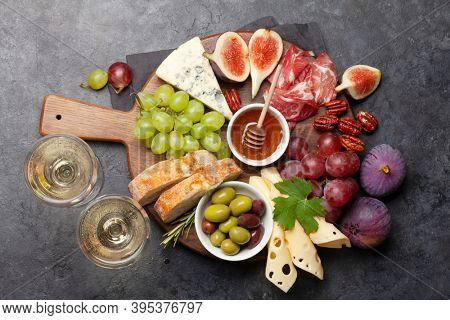 Antipasto plate with prosciutto, cheese, figs and grapes. Appetizer board and white wine. Top view flat lay