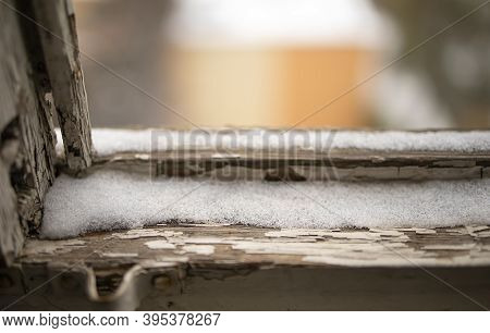 Layer Of Ice On A Windowsill With Snow On Top. The Snow Falls On The Old Windowsill. Close-up