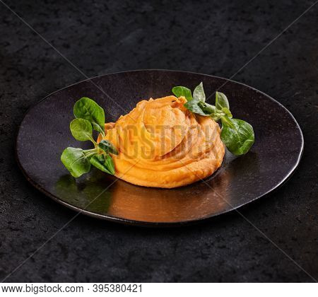 Portion Of Mashed Potatoes With Roasted Pepper In Black Plate, Dark Background.