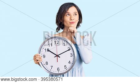 Young beautiful girl holding big clock serious face thinking about question with hand on chin, thoughtful about confusing idea