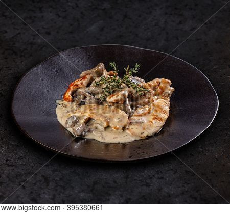 Chicken Grilled Breast Stewed In Cream Sauce With Mushrooms On Bark Background