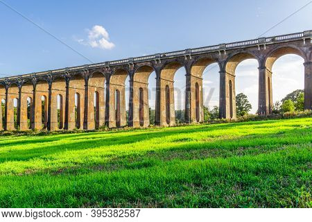 A View Of The Ouse Valley Viaduct (balcombe Viaduct) In The Summer With Bright Sun Shining Through T
