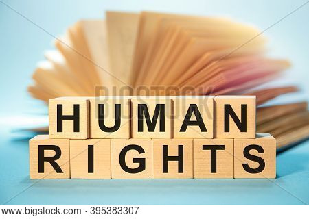 Wooden Cubes With The Abbreviation Human Rights On The Background Of An Open Book.