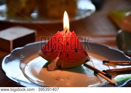 Melted Candle In Shape Of Triangle Piece Of Watermelon. Candlelight Flame Closeup. Burning Fire Of C