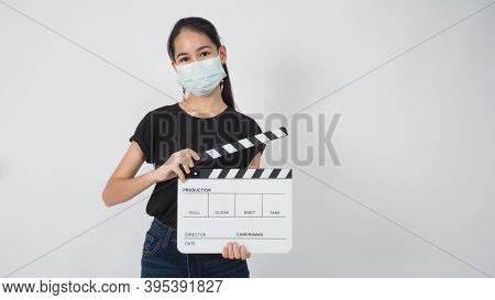 Teenage Girl Or Young Woman Wear Face Mask And Hand\'s Holding Clapper Board Or Movie Slate Use In V