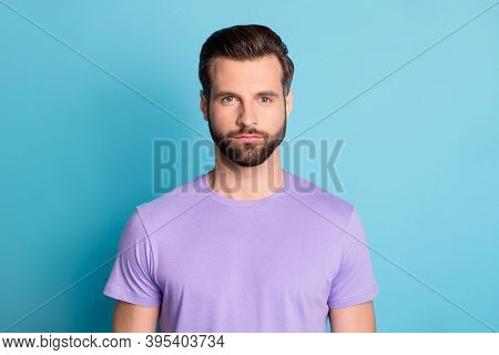 Portrait Of Young Handsome Serious Reliable Male Look Camera Wear Violet T-shirt Isolated On Blue Co