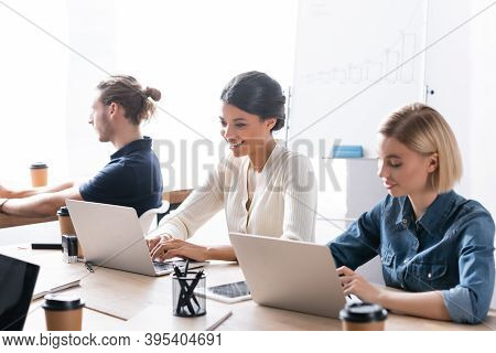 Multicultural Female Co-workers Typing On Laptops While Sitting At Desk Near Colleague In Office