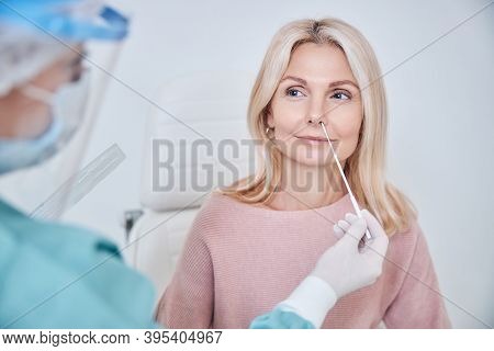 Nurse Inserting The Swab Into The Woman Nostril