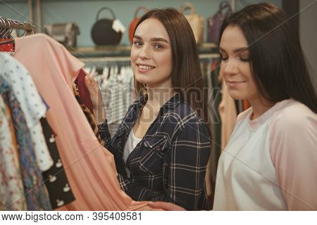Lovely Cheerful Woman Smiling To The Camera, While Shopping For Clothing With Her Friend. Two Female