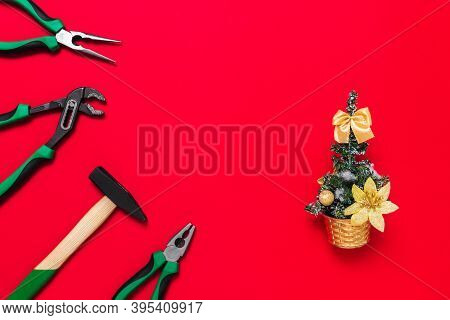 A Set Of Quality Green Building Tools To Repair A Car Or House And Christmas Tree On A Red Backgroun
