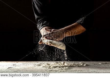 Male Hands Making Dough For Pizza. Pizza Dough. Cooking Bread. Kneading The Dough. Isolated On Dark