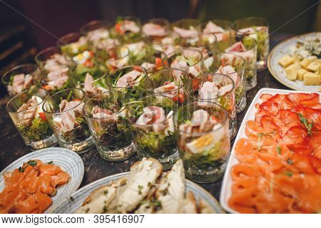 Glass Glasses And Plates With Meat And Fish Appetizers In A Restaurant. Snack With Red Fish, Cheese,