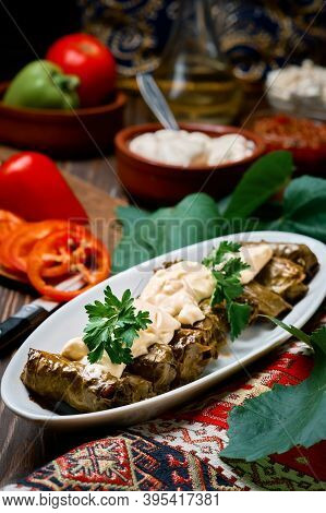 Mediterranean Cuisine - Dolma In Plate With Fresh Cilantro And Sauce On Dark Wooden Table, Close-up