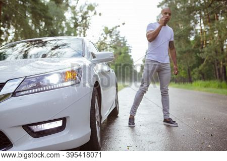 Man Calling Roadside Assistance For His Broken Down Car, Selective Focus On Automobile On Foreground