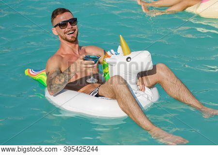 Handsome Young Tattooed Man Laughing Joyfully Swimming On Inflatable Unicorn At The Pool. Cheerful M