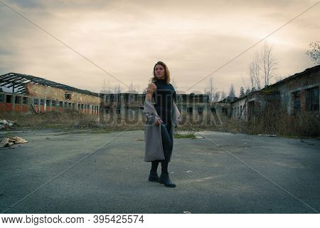 A Woman On The Ruins In A Ruined City With Garbage.