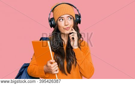 Beautiful brunette young woman wearing student backpack and holding books serious face thinking about question with hand on chin, thoughtful about confusing idea