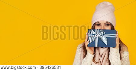Happy Young Woman With A Gift Box In Her Hands, Covers Half Of Her Face With A New Years Gift. The G