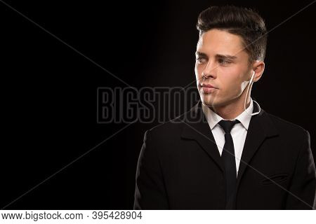 Handsome Young Professional Bodyguard Looking Suspiciously At The Copyspace On The Side Black Backgr