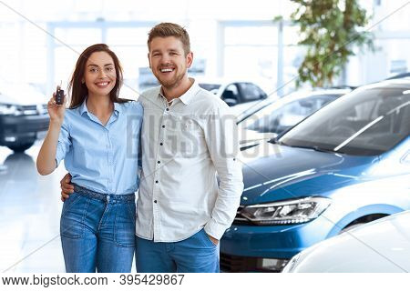First Big Buy Together. Portrait Of A Happy Young Couple Hugging In A Car Salon Showing Car Keys To