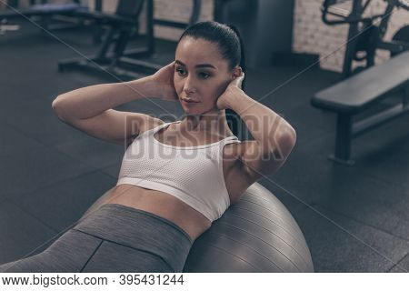 Beautiful Fit Woman Doing Abs Crunches On Fitness Ball, Working Out At The Gym. Attractive Fitness F