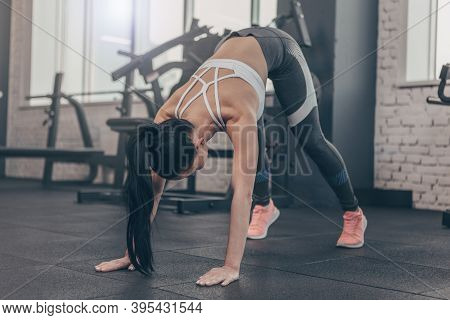 Dark Haired Fit Sportswoman Stretching Her Body Before Workout At The Gym, Copy Space. Fitness Femal