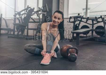 Full Length Portrait Of A Beautiful Happy Healthy Woman Tying Her Shoelaces, Sitting On The Gym Floo