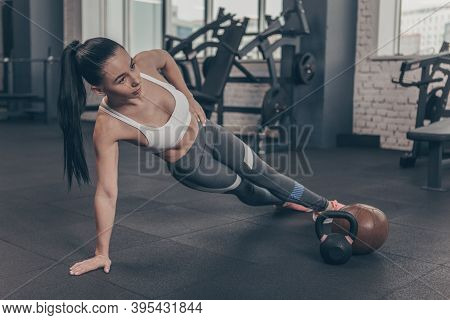 Full Length Shot Of A Beautiful Dark Haired Athletic Woman Exercising At The Gym, Doing Side Plank,