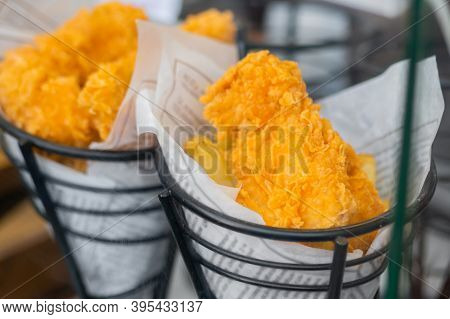 Crispy Fried Fish Or Chicken Meat In Batter Wrapped In Newspaper At Summer Outdoor Food Market: Clos