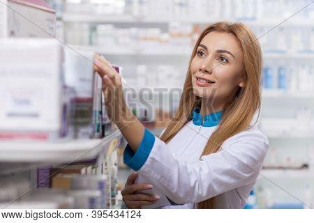 Beautiful Confident Female Pharmacist Smiling Joyfully, Organizing Medical Products On Sale On The D