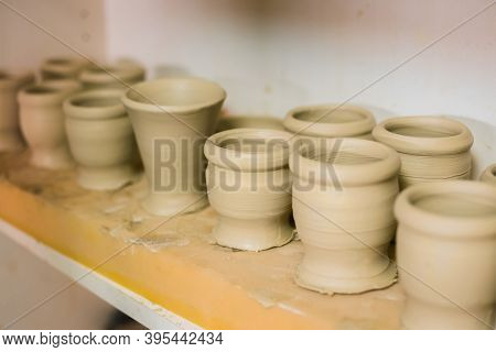 Crafting, Diy, Artwork And Handmade Concept. Unfinished Mugs In Row On Shelf Of Pottery Workshop, Ce