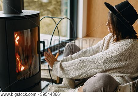 Stylish Woman In Knitted Sweater And Hat Warming Up At Modern Black Fireplace. Cozy Home