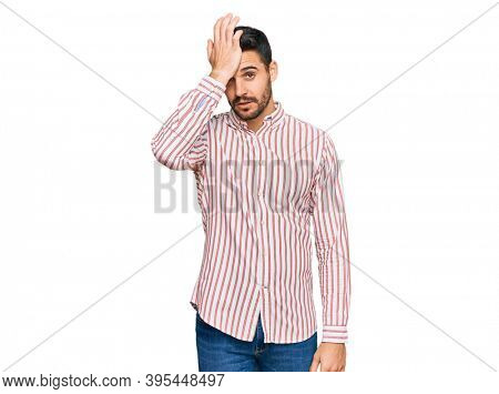 Young hispanic man wearing business shirt surprised with hand on head for mistake, remember error. forgot, bad memory concept.