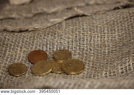 Coins On The Burlap Canvas Texture. Money And Finance Concept