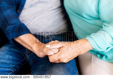 Senior Couple Holding Hands Sitting Together At Home, Faces Is Not Visible. Concept Of Support And C