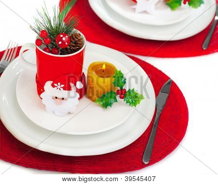 Photo of beautiful Christmastime table setting, holiday banquet, christmas celebration, luxury white porcelain dishware on red festive tablecloth, candle and little toys decorated utensil for dinner