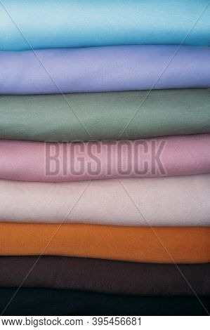 Stack Of Pastel Natural Color Fabrics On White Background. Fabrics And Clothing Arranged In Neat Sta
