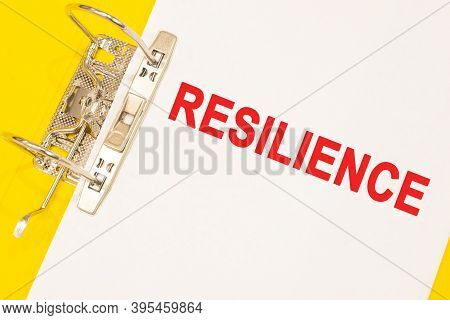 The Word Resilience On A White Background With A Yellow Folder. Business Concept