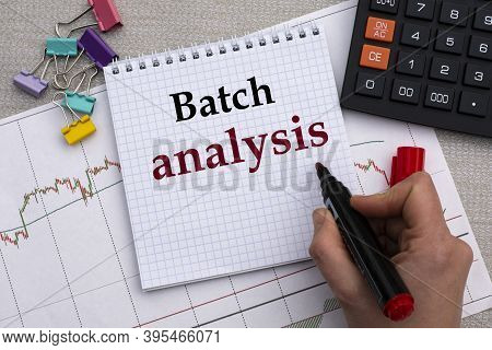 A Woman's Hand Writes In A Notebook The Words Batch Analysis On The Background Of A Graph, Calculato