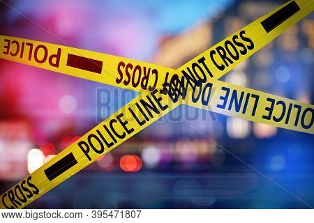 Yellow Law Enforcement Tape Isolating Crime Scene. Blurred View Of City, Toned In Red And Blue Polic