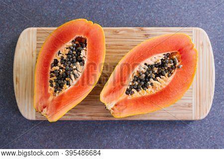 Simple Food Ingredients, Fresh Papaya Fruit Cut In Halves On Top Of Cutting Board