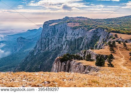 A Majestic View Of The Rocky Mountains And The Valley In Fog And Clouds. Creamy Fog Covered The Moun