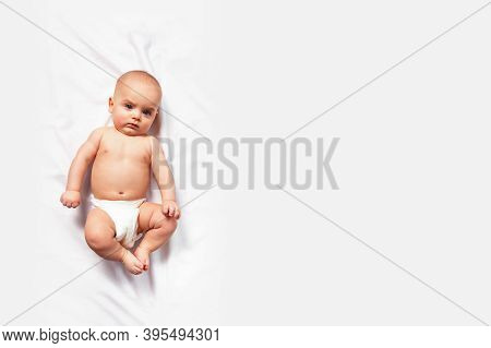 Banner With Caucasian Funny Child In White Nappy Lies On Light Background. Copy Space. Top View. Chi