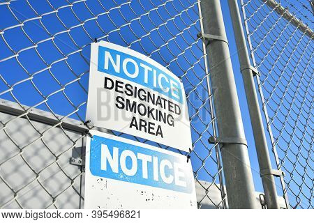 An Image Of A  Blue And White Designated Smoking Area Sign Posted To A Chain Link Fence.