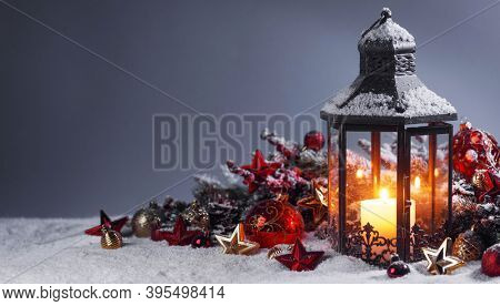 Christmas composition of lantern colorful ornaments balls stars candles and fir tree branches on snow