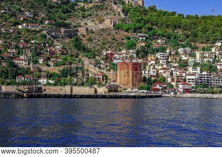 Alanya Coastline With Modern Cottages, An Ancient Wall And Red Tower On The Side Of A Mountain Again