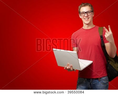 man holding laptop and backpack isolated on red background