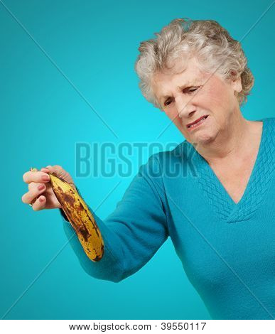 Senior woman holding a rotten banana over blue background