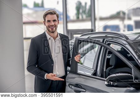 Smiling Brown-haired Male Presenting New Car, Holding Car Door